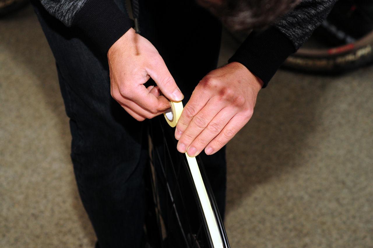 Első lépésként lekerül a felniről a külső, a belső és a felniszalag is, majd a szettben található vékony szalagot felragasztjuk a felniszalag helyére, úgy, hogy az a küllőnyílásokat takarja, és a szelepnyílást is befedje. Forrás: Paraferee - Mozgásvilág.hu