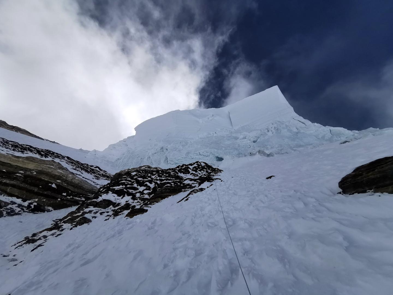 Az ember feje fölött kifelé dőlve tornyosul a 120 m magas jégfal, a Palacknyak-kuloár Forrás: Eseményhorizont