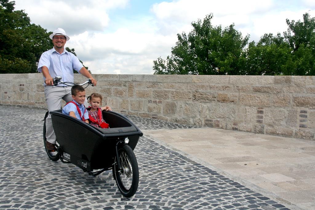 Gyermekszállítás vidáman és felsőfokon. Forrás: www.mozgasvilag.hu